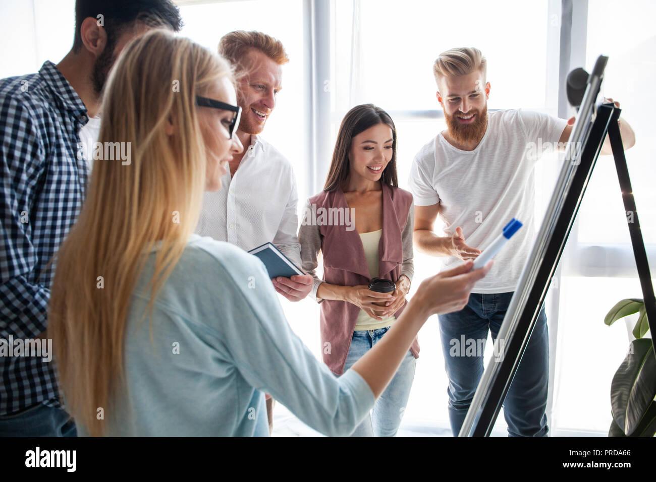Grupo de jóvenes colegas vestidos casual de pie juntos en la oficina moderna y la reflexión. Imagen De Stock