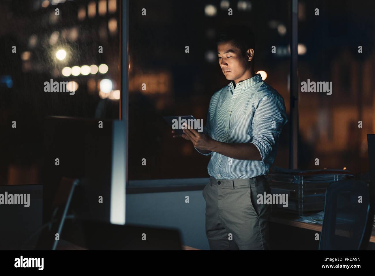 Empresario asiático utilizando una tableta digital a altas horas de la noche Foto de stock