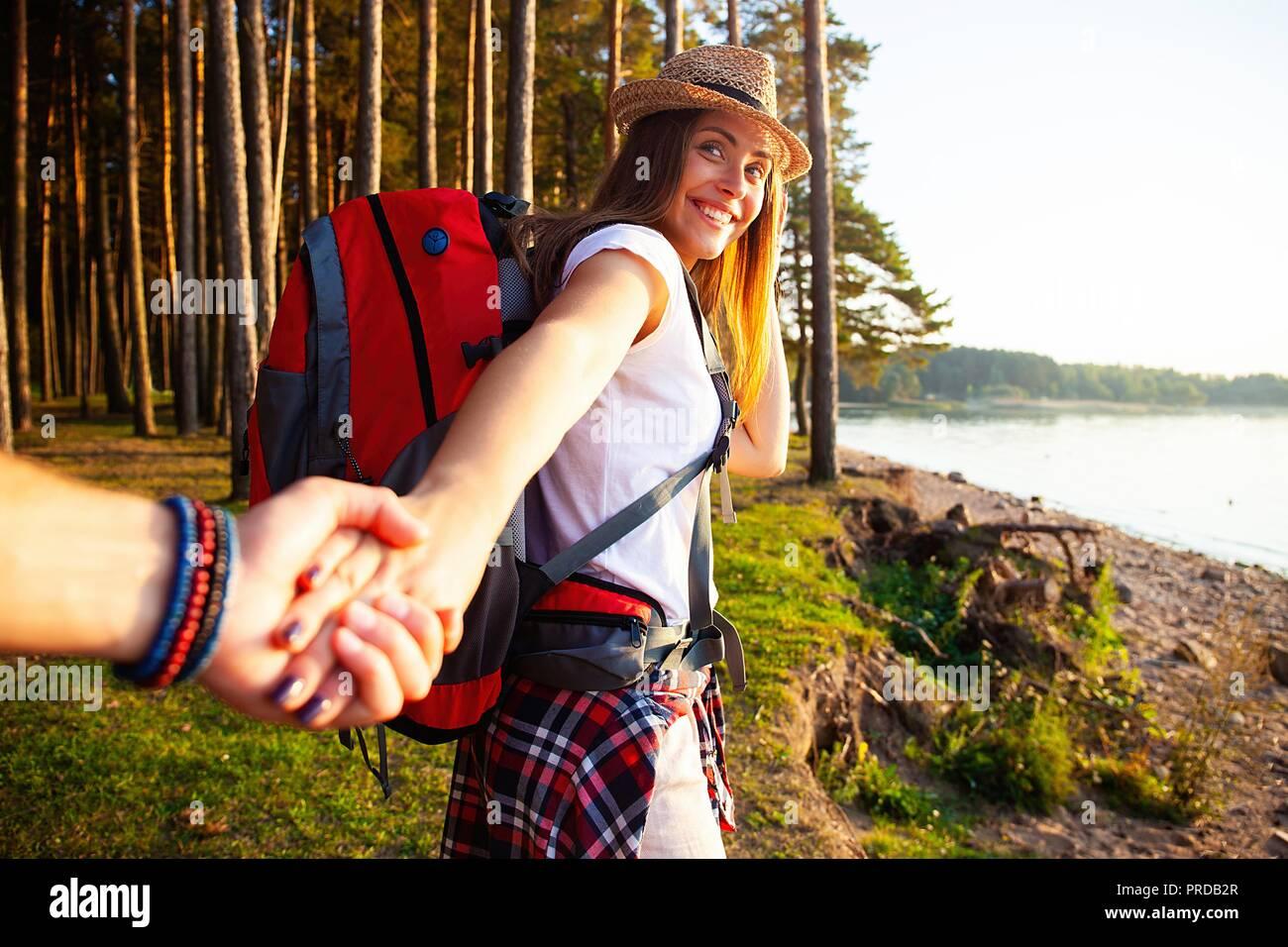 Retrato de mujer joven feliz sosteniendo la mano de su novio mientras caminaba en el bosque. Foto de stock