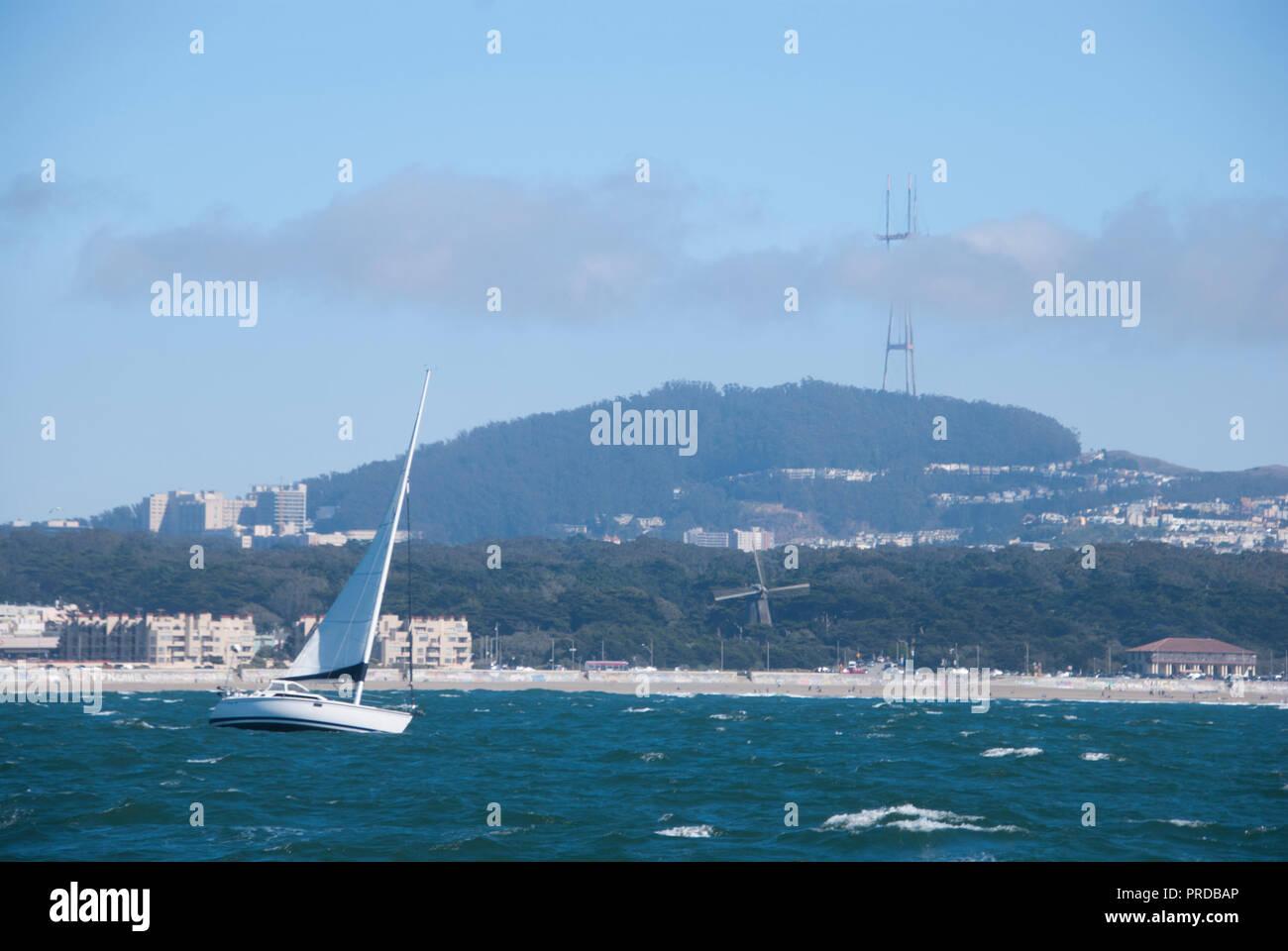 Un velero en el océano Pacífico frente a la costa de San Francisco con Sutro torre visible detrás de él. Foto de stock
