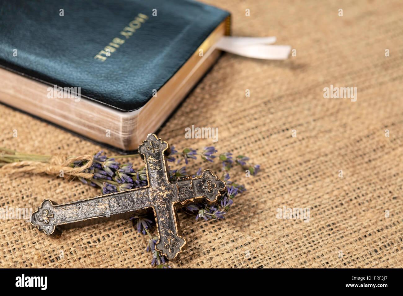Primer plano de una cruz cristiana metálica sobre la lavanda flores junto a la Santa Biblia sobre fondo textil. Imagen De Stock