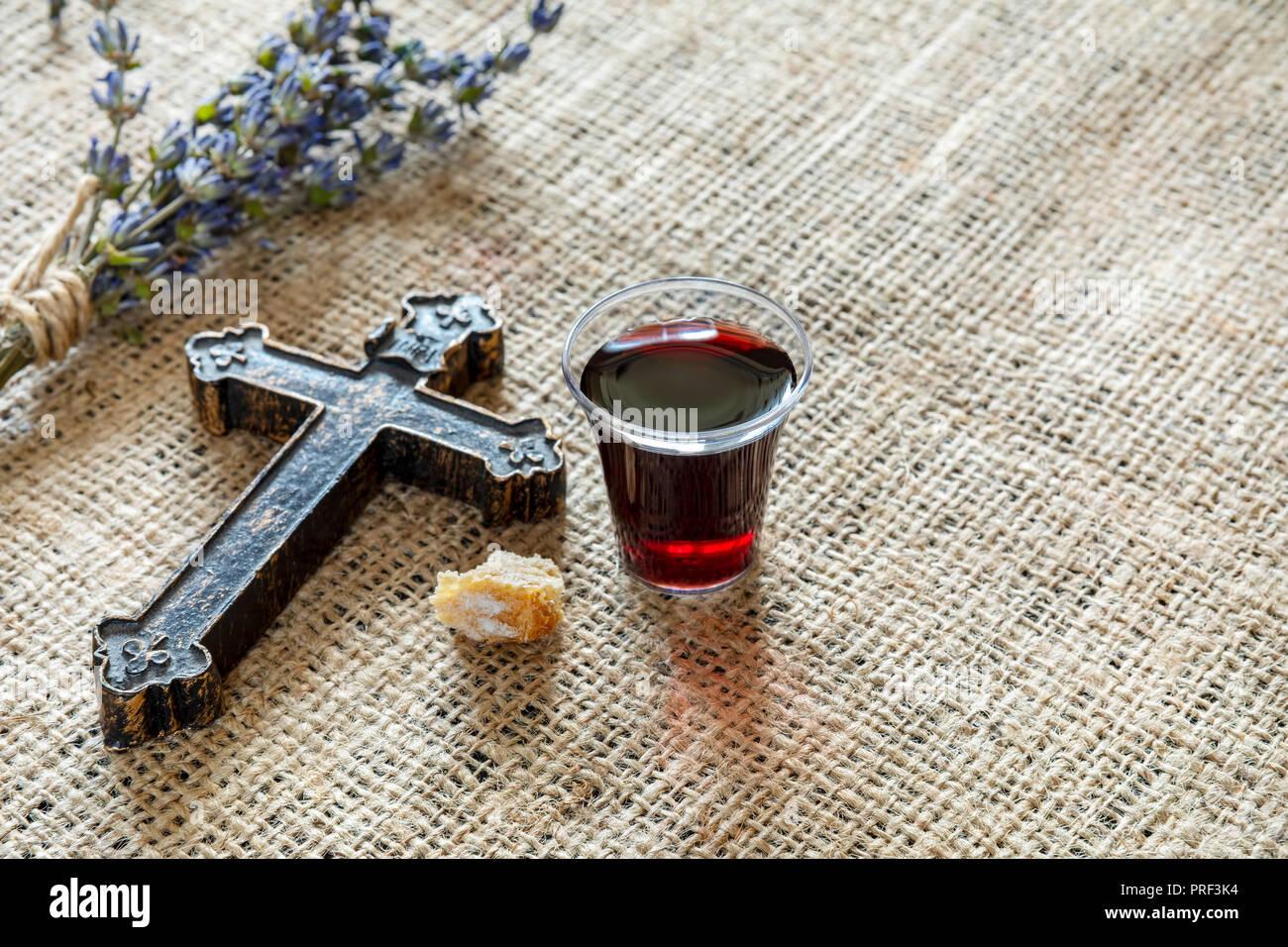 Teniendo comunión con copa de vino y pan, cerca de cruz y lavanda en el mantel de textiles. Imagen De Stock