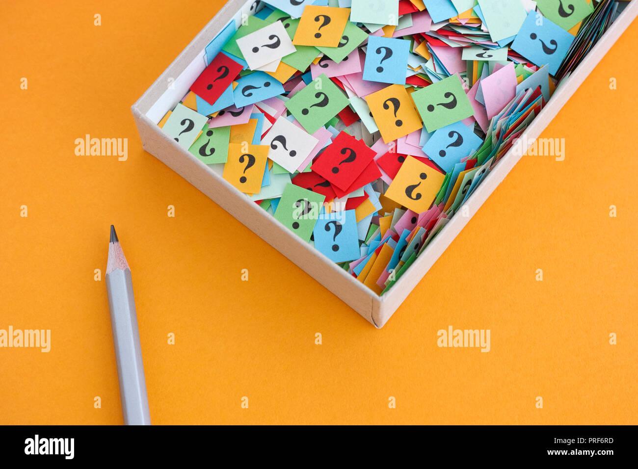 Lápiz y signos de interrogación en una caja de papel sobre fondo amarillo. Concepto imagen. Cerca. Foto de stock