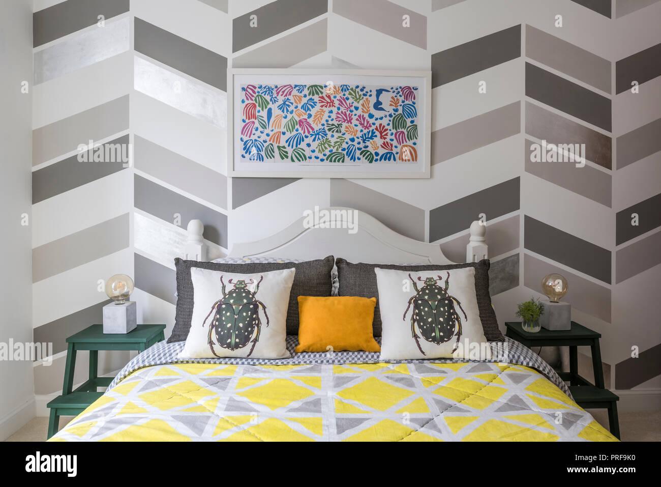 Surtido de patrones geométricos en dormitorio con cojines de escarabajos Imagen De Stock