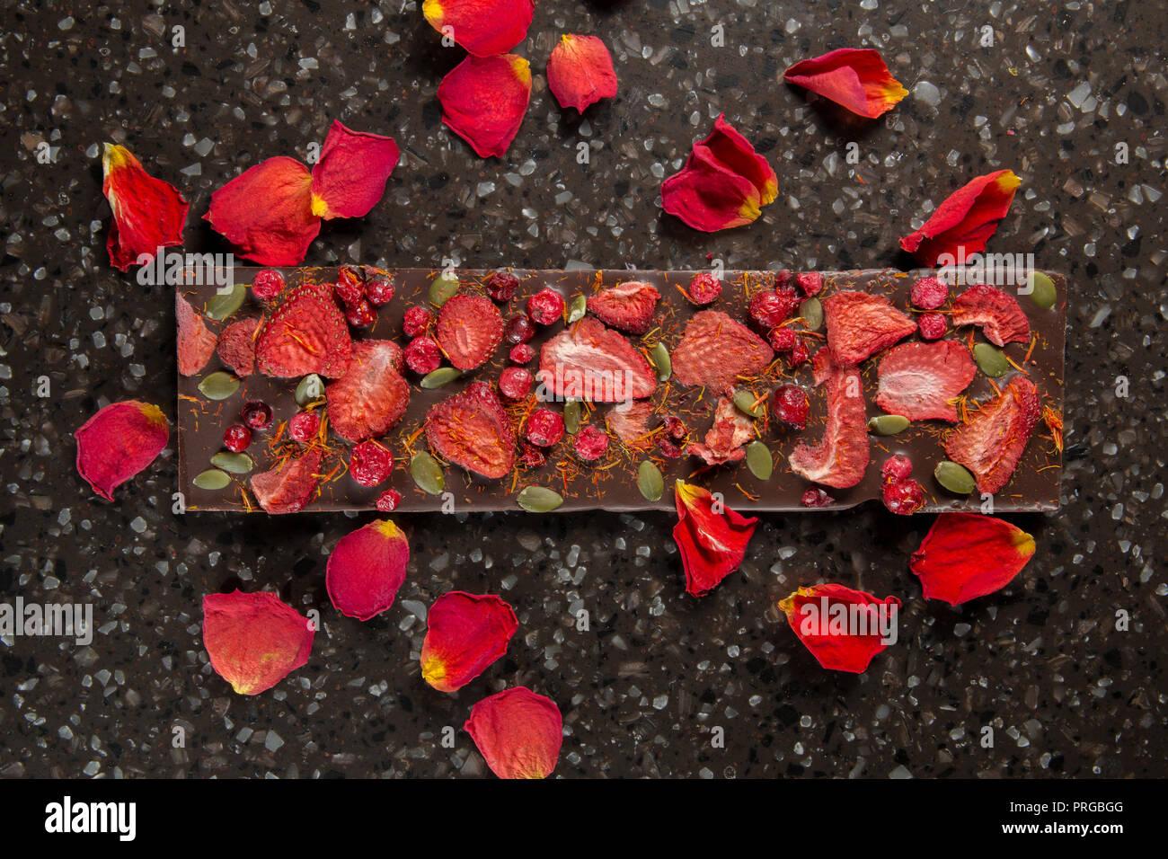Barra de chocolate casero con fresas y arándanos secos en pétalos de rosa. Foto de stock
