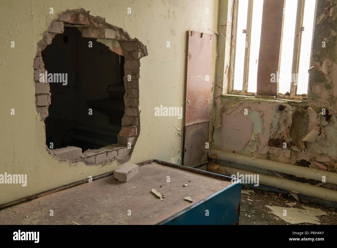 El agujero perforado a través de la pared de la celda de una prisión para una escapada. Foto de stock