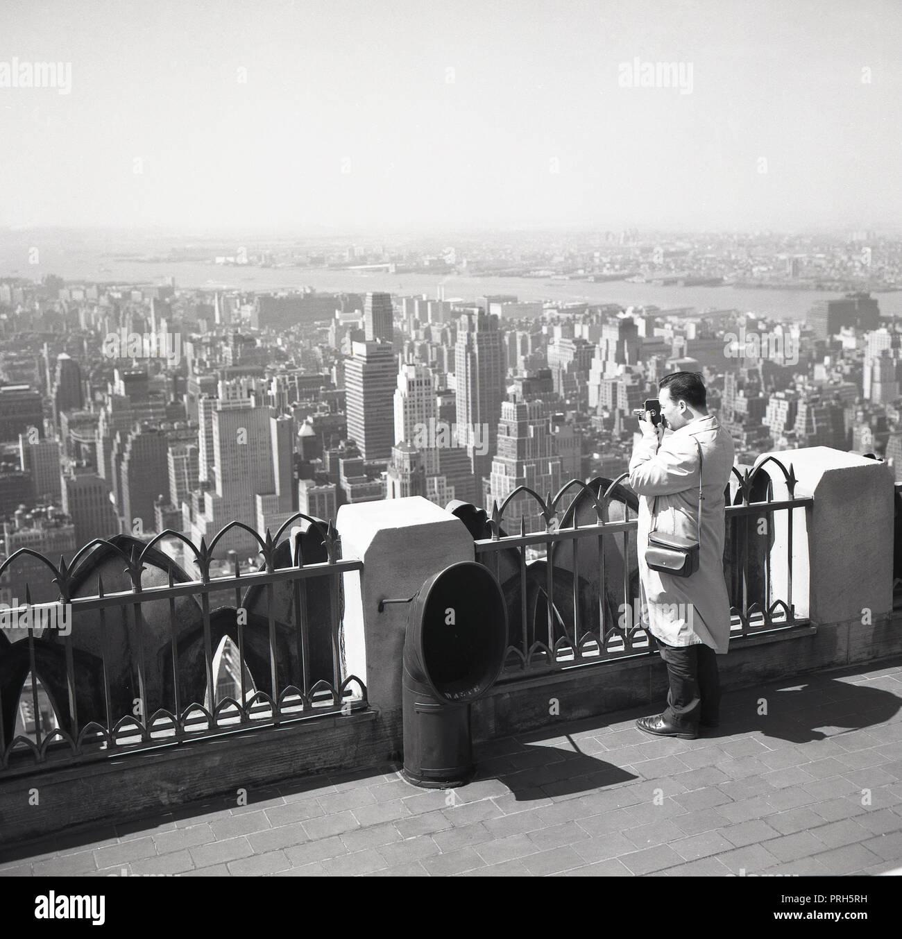 1950, histórico, el hombre con una cámara para filmar una película de cine y vistas al horizonte de la ciudad de Nueva York desde la cima del Empire State Building, Nueva York, NY, EUA. Imagen De Stock