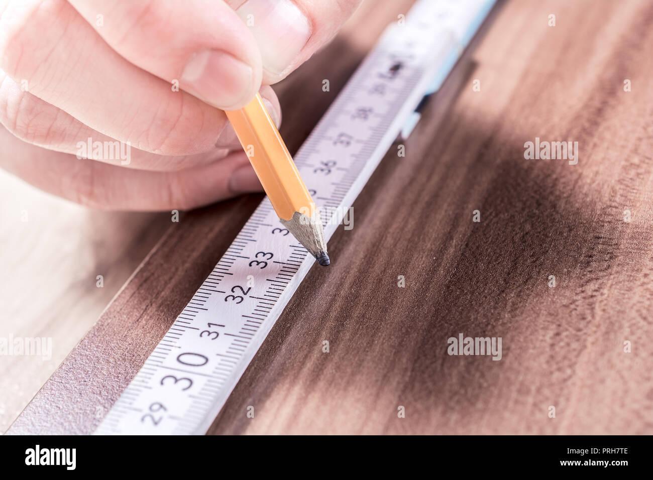 Hombre Mano haciendo una marca en el punto de medición de un patrón de plegado sobre una tabla de madera Imagen De Stock