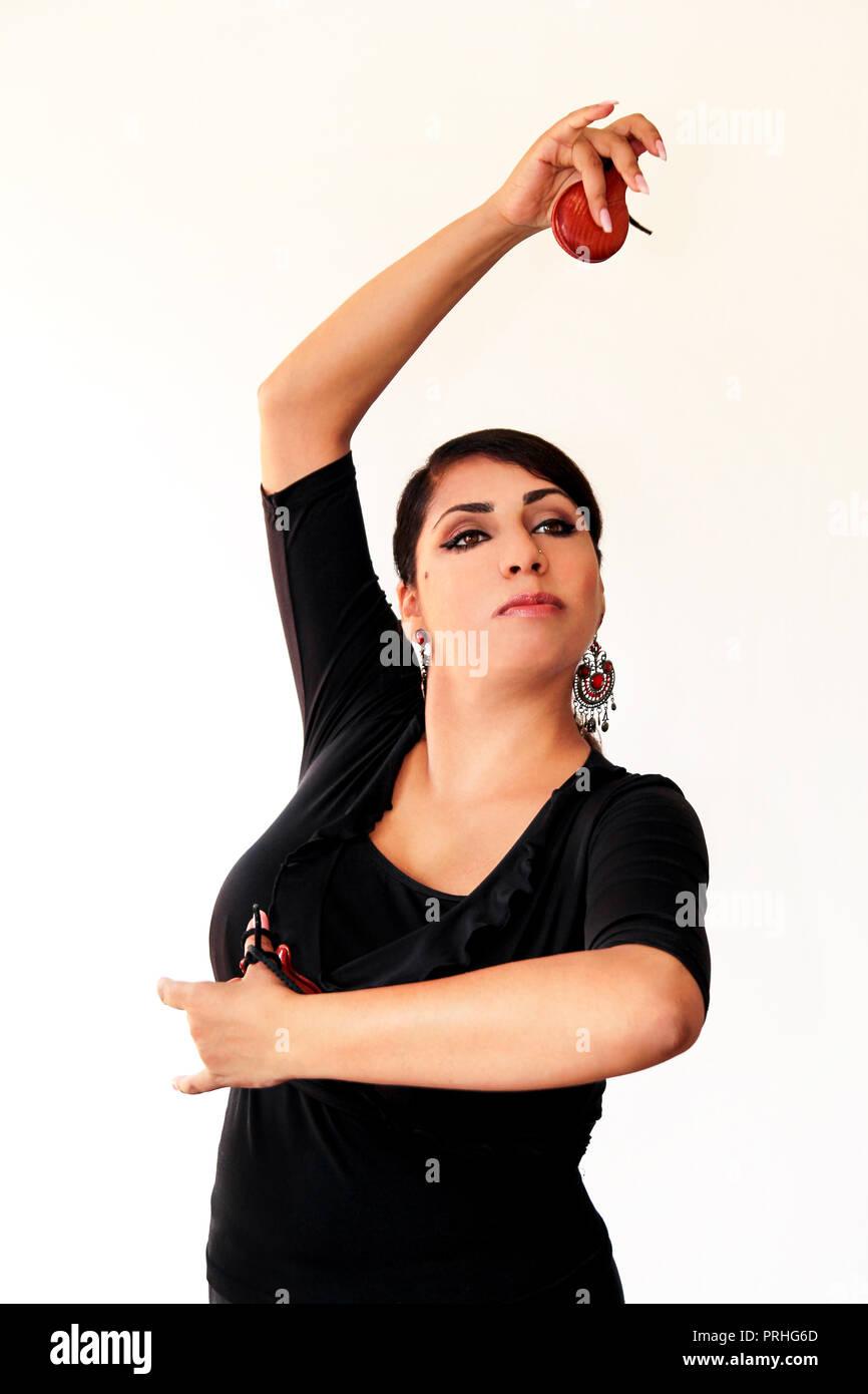 Joven mujer gitana española bailando flamenco con castañuelas marrón en sus manos. El bailarín de flamenco en el hermoso vestido nacional sobre un fondo blanco. España Imagen De Stock