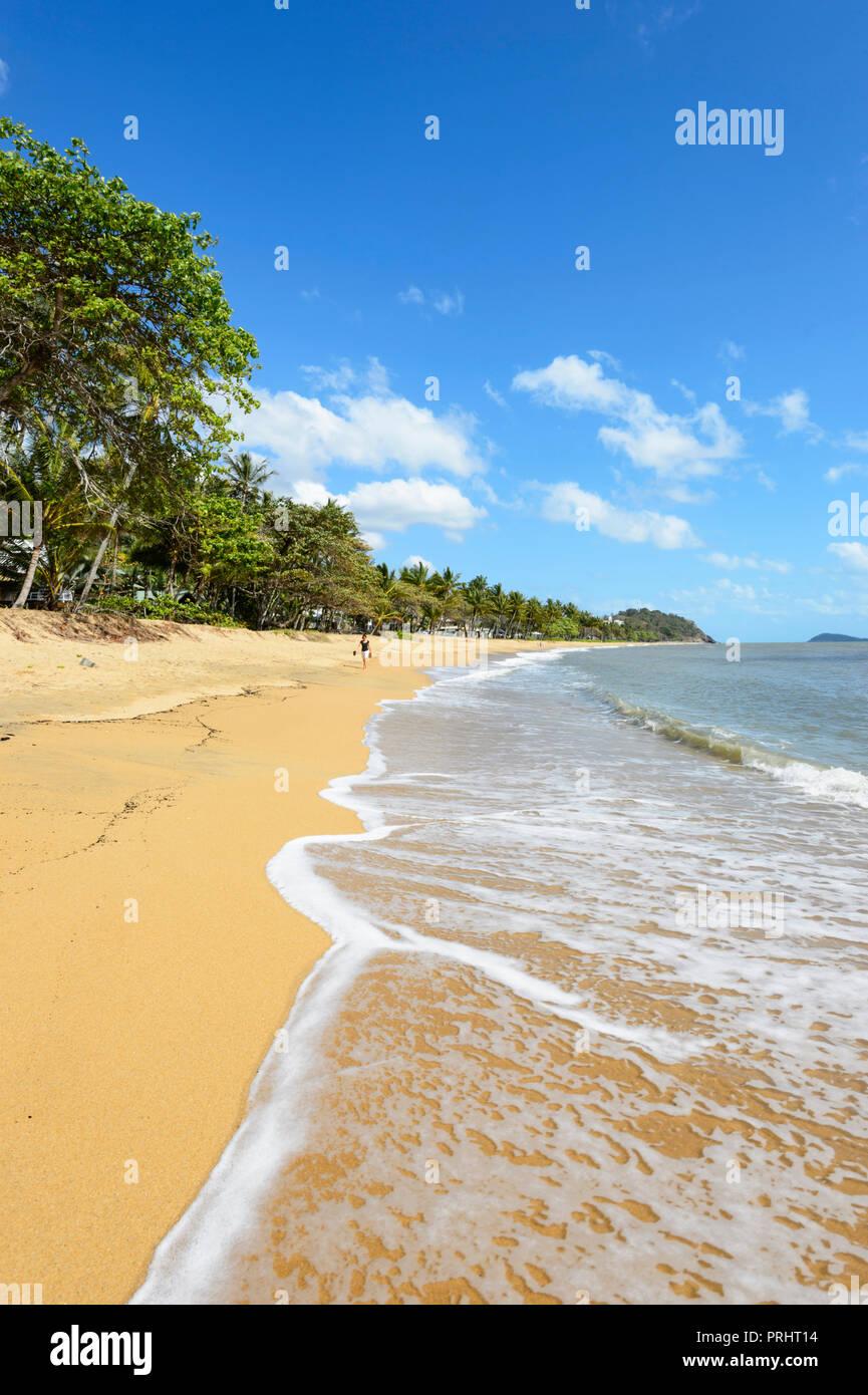 Persona caminando por la playa en Trinity Beach, playas del norte de Cairns, Far North Queensland, FNQ, Queensland, Australia Imagen De Stock