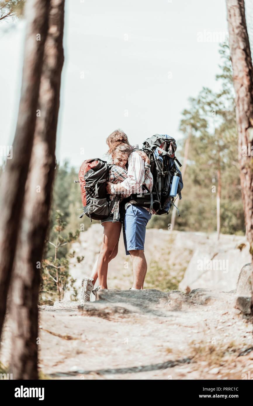 Tierna mujer con mochila pesada abrazando su fuerte hombre barbado mientras senderismo Imagen De Stock