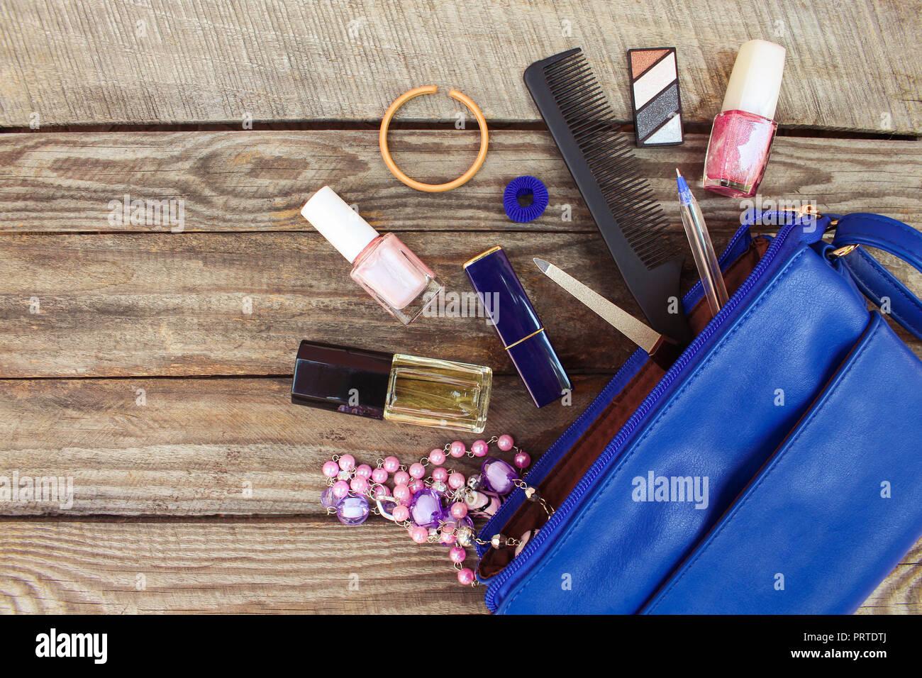 d6ae22201 Cosas de abrir dama Bolso Bolso de mujeres sobre madera de fondo. Cosméticos  y accesorios para la mujer cayó del bolso azul. Imagen de tonos.