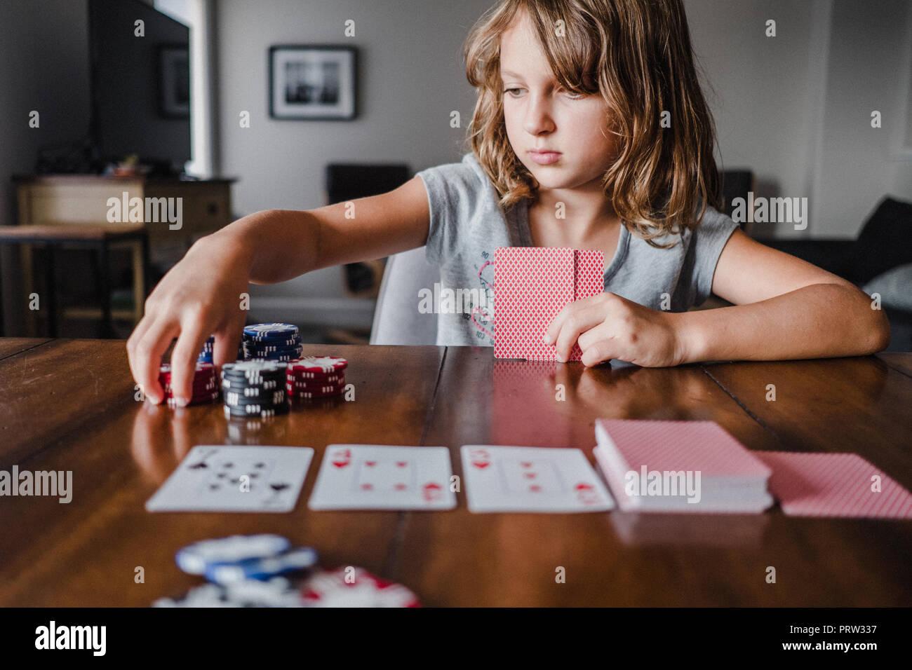 Chica jugando a las cartas en la mesa, apilando fichas de juego Imagen De Stock