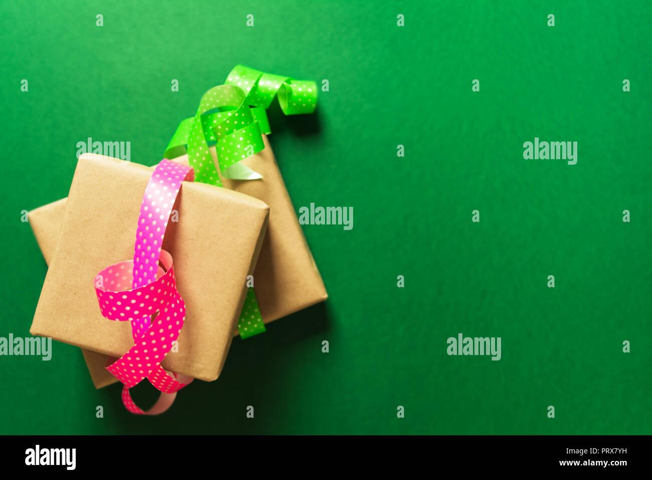 Envolver los regalos en papel artesanal con cintas sobre fondo verde, laicos plana Imagen De Stock