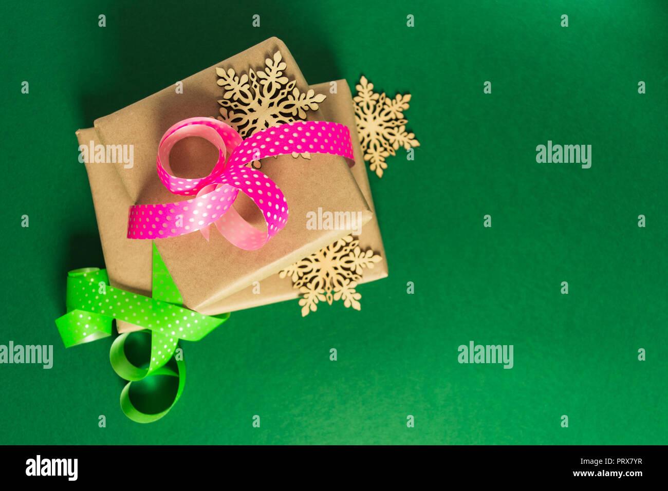Regalos de Navidad y Año Nuevo listos para el embalaje de madera con copos de nieve sobre fondo verde, plana lay, vista superior Imagen De Stock