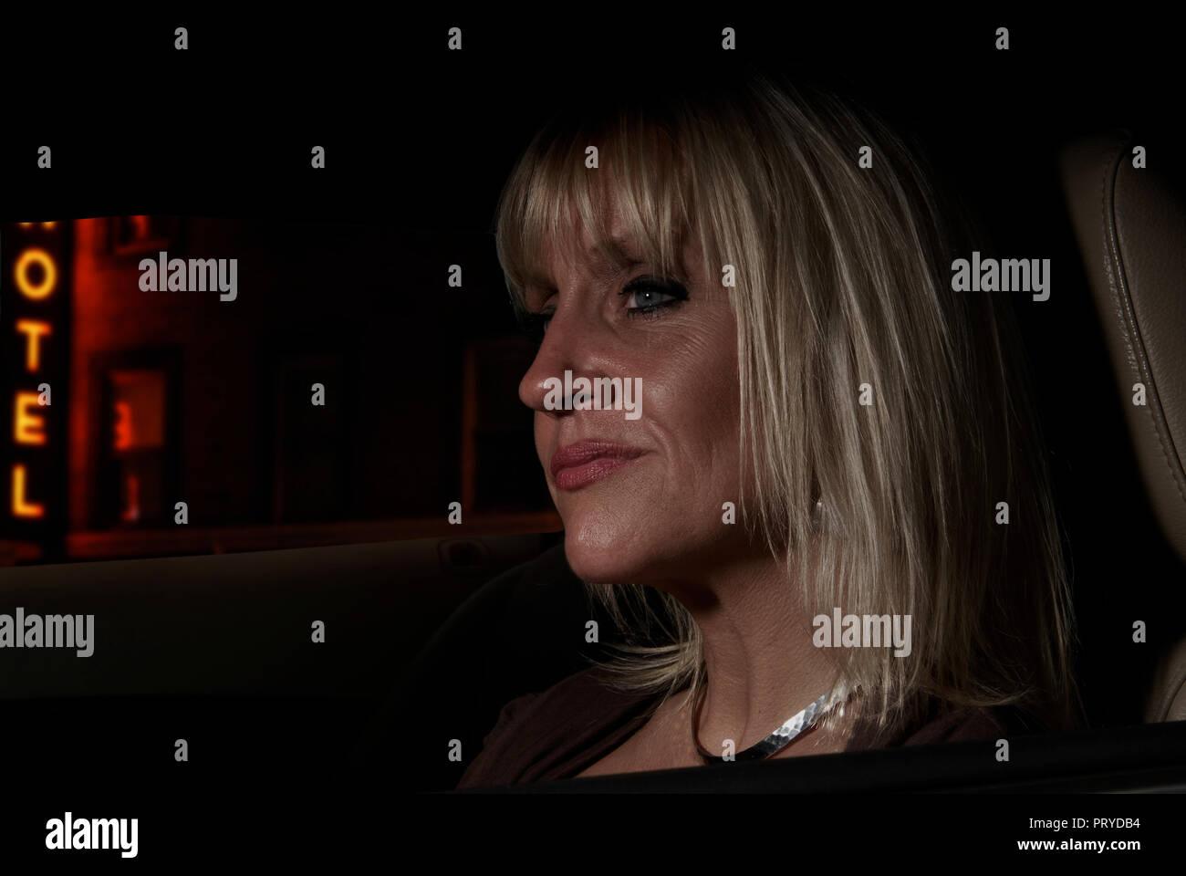Fotografía conceptual de una mujer en un coche de noche fuera de un hotel, como si la comprobación de su marido. Exclusivo. Derechos gestionados Foto de stock