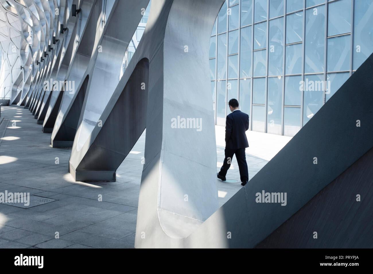 China, Shenzhen, moderna arquitectura y empresario caminando Foto de stock