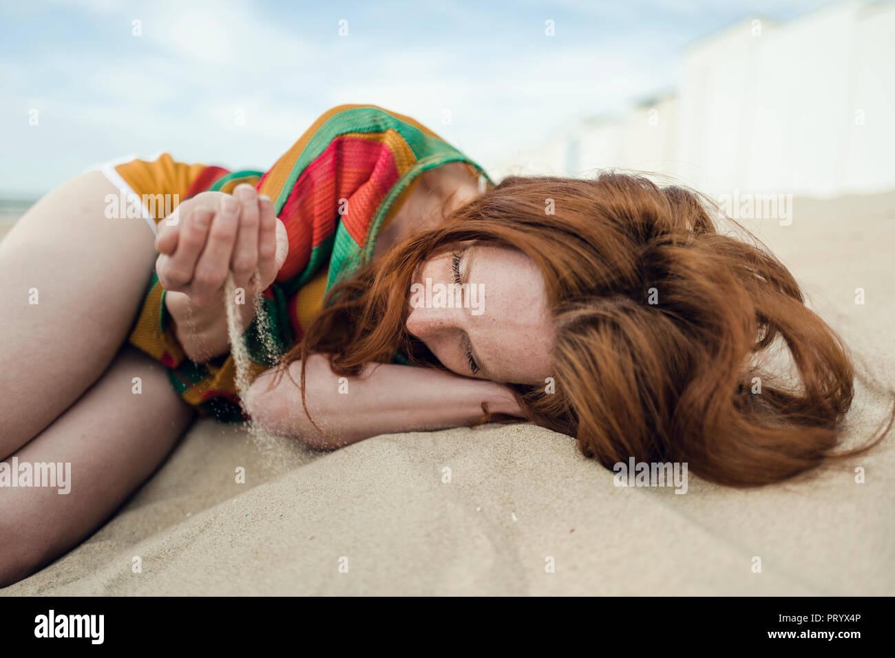 Pelirroja mujer acostado en la playa con arena goteando a través de su mano Foto de stock