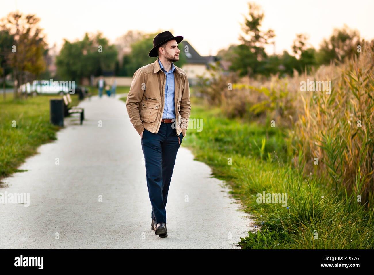 Apuesto hombre elegante en el parque llevar chaqueta y sombrero Fedora.  Imagen De Stock 927467b0a30