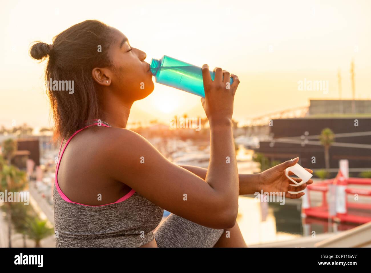 Mujer joven agua potable durante el trabajo fuera Foto de stock