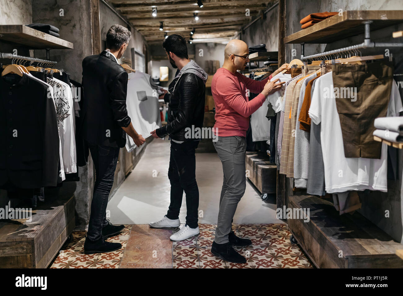 c0f36dbfe Tres hombres en la moderna tienda de ropa de hombre con la nueva ...