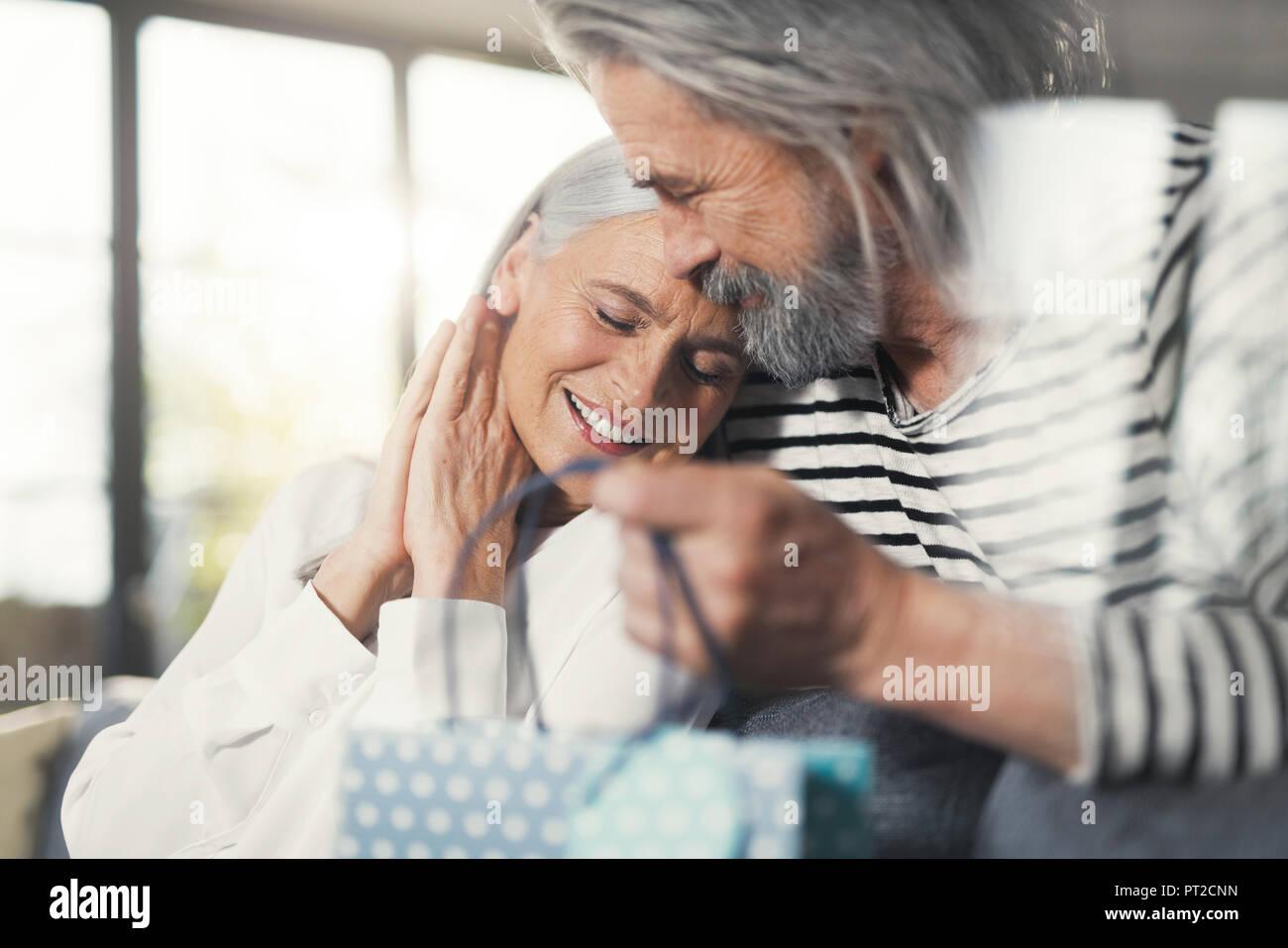 Hombre Senior sorprendente esposa con un regalo Imagen De Stock
