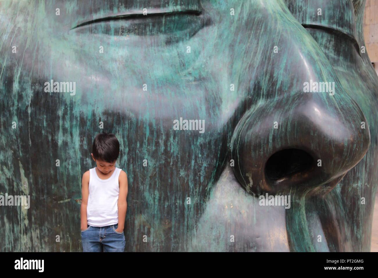 Niño vestido con camiseta blanca posando junto una enorme escultura de rostro en color verde en un día soleado en el centro de Guadalajara Imagen De Stock