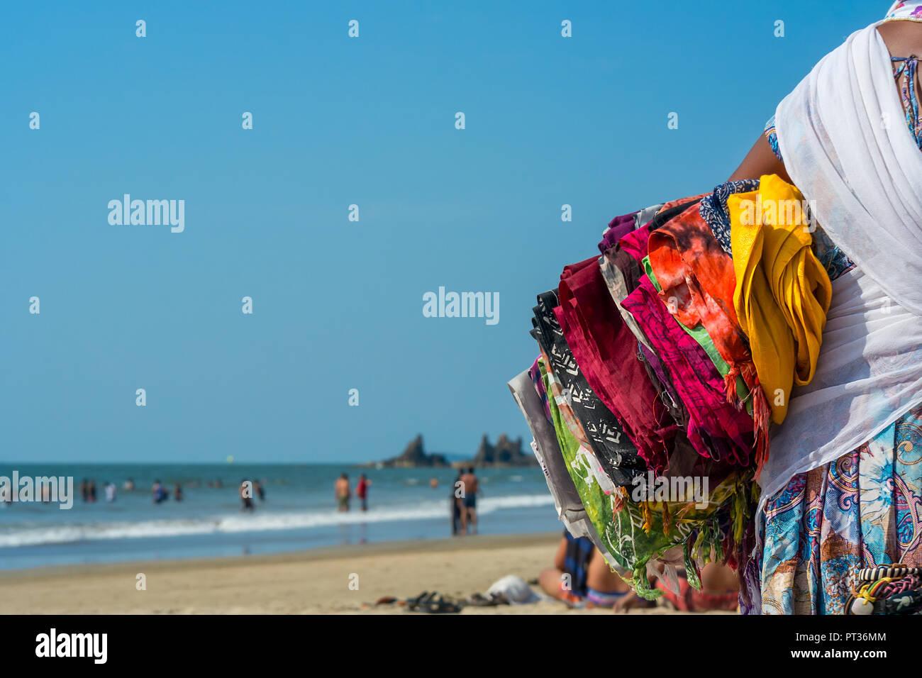 651fe224cbf0 Una señora india local lleva coloridos sarongs bajo su brazo como ella  tratar de venderlos a