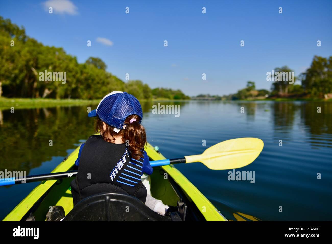 Niños remando en una canoa en el clima hermoso, Ross River QLD, Australia Foto de stock