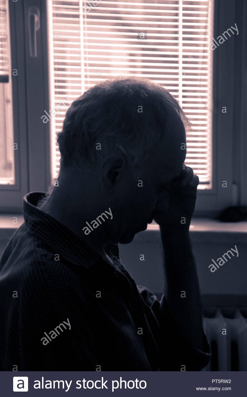 Hombre sentado y sosteniendo una mano sobre su rostro en la depresión y la tristeza Imagen De Stock