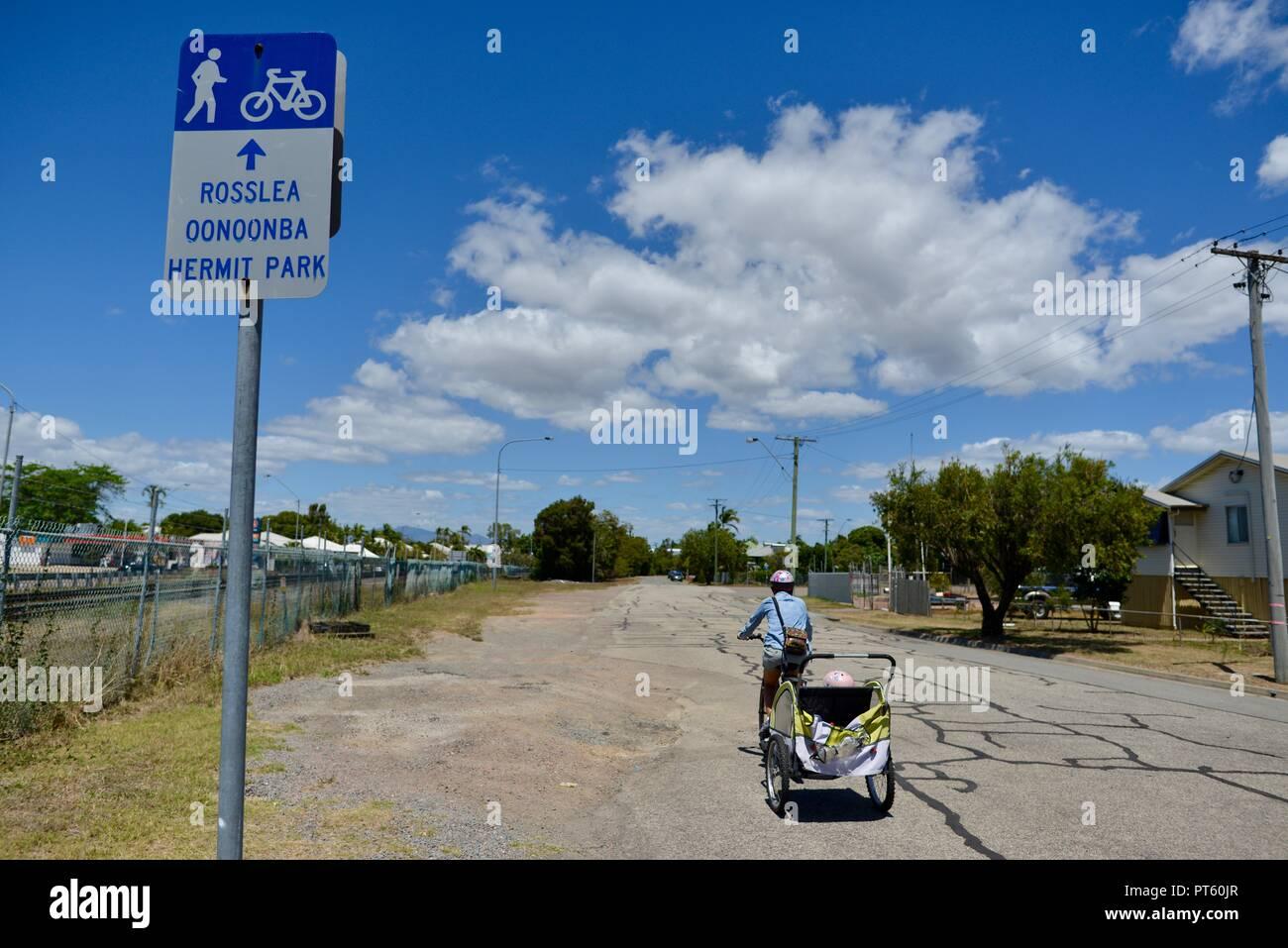 Mujer en bicicleta con un remolque de bicicleta para niños, Townsville, Queensland, Australia Foto de stock
