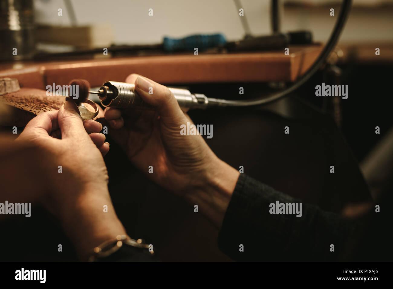 6dab77489e83 Hembra madura jeweler pulir un anillo de oro en el banco. Goldsmith  haciendo un anillo