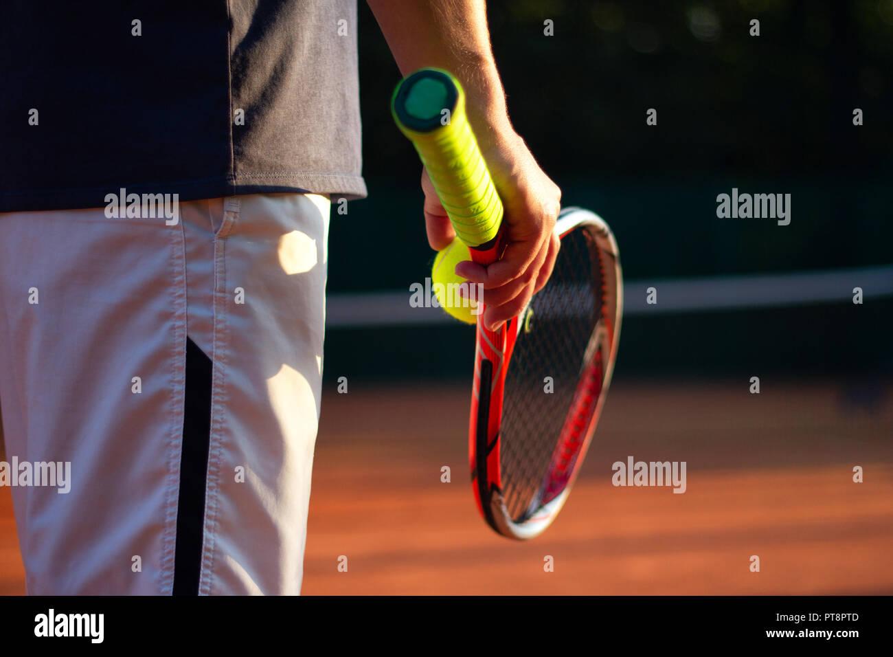 Un jugador de tenis se prepara para servir una pelota de tenis durante un partido Foto de stock