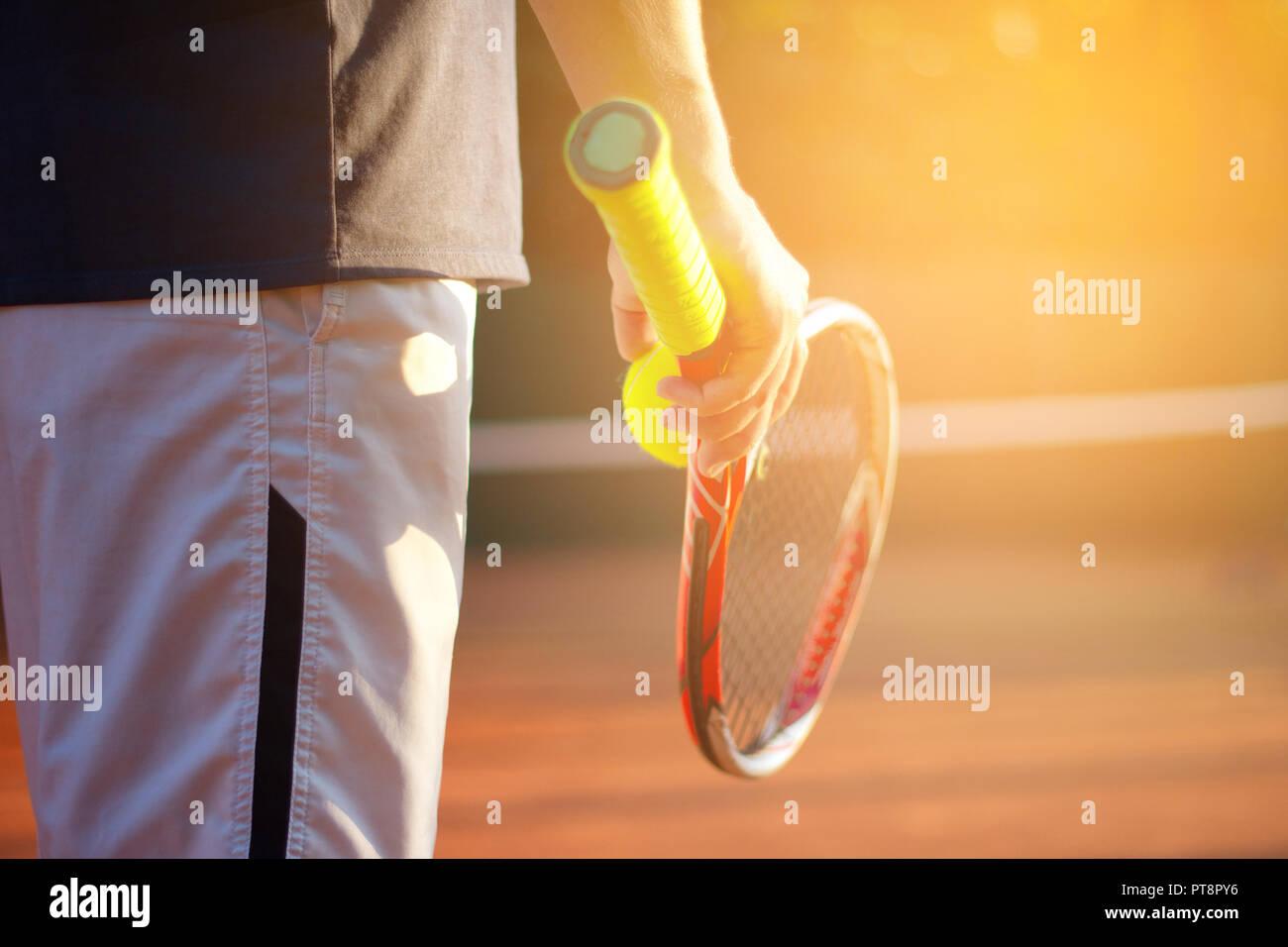 Un jugador de tenis se prepara para servir una pelota de tenis durante un partido na dhold el balón con cohete en la mano derecha. La luz del sol en segundo plano. Foto de stock