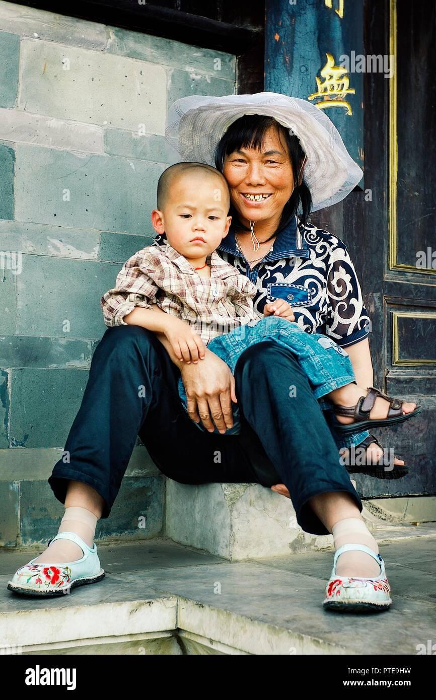 China / Pekín - jun 24 2011: una joven madre con su niño delante de las puertas de un templo Foto de stock