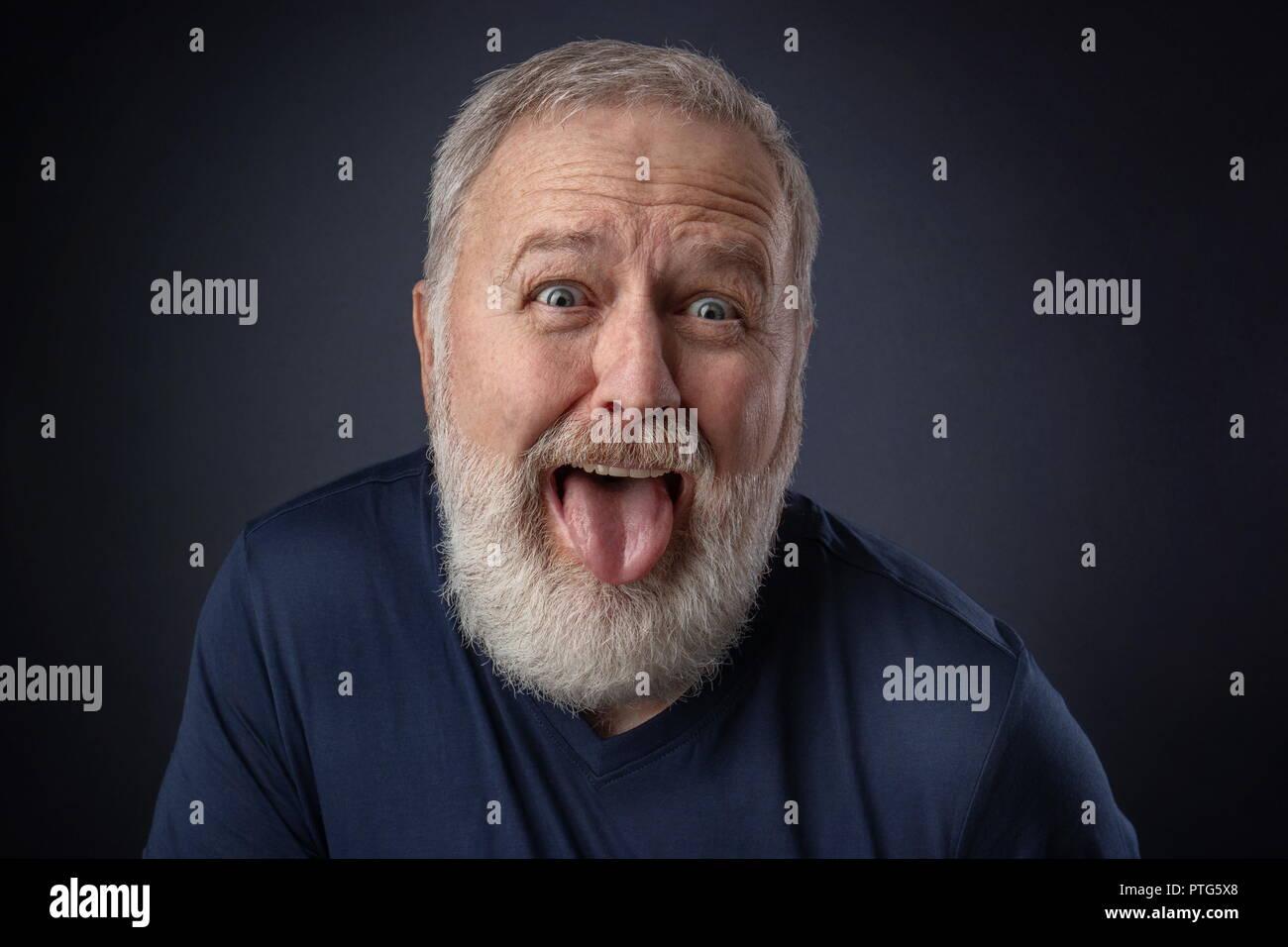 Retrato de un hombre viejo haciendo una horrible mueca y tirando de la lengua fuera Imagen De Stock
