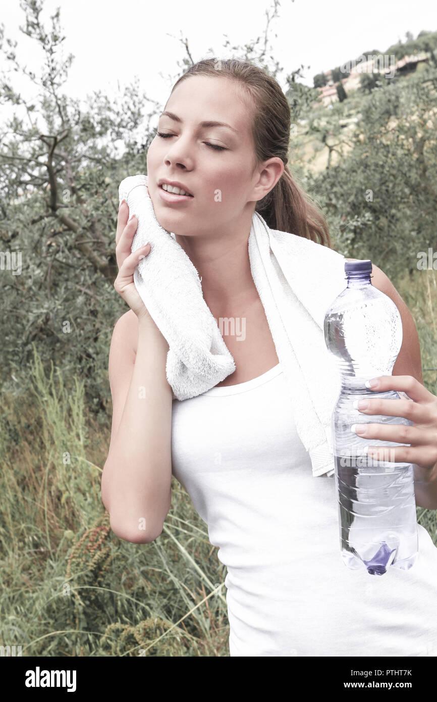 Sportliche junge Frau trinkt Wasser aus einer Flasche, trocknet sich mit dem Handtuch ab, Deportivo joven de beber agua de una botella, se seca fuera w Imagen De Stock