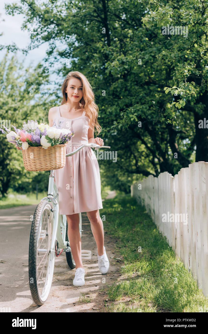 dbc8c9a7e6 Joven Mujer hermosa en el vestido con retro-bicicleta con cesta de mimbre llena  de flores en campo