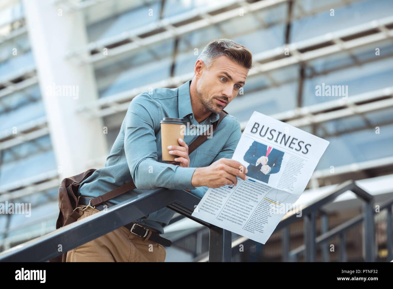 Conmocionó a un varón de mediana edad la celebración de café y leer el periódico de negocios Foto de stock