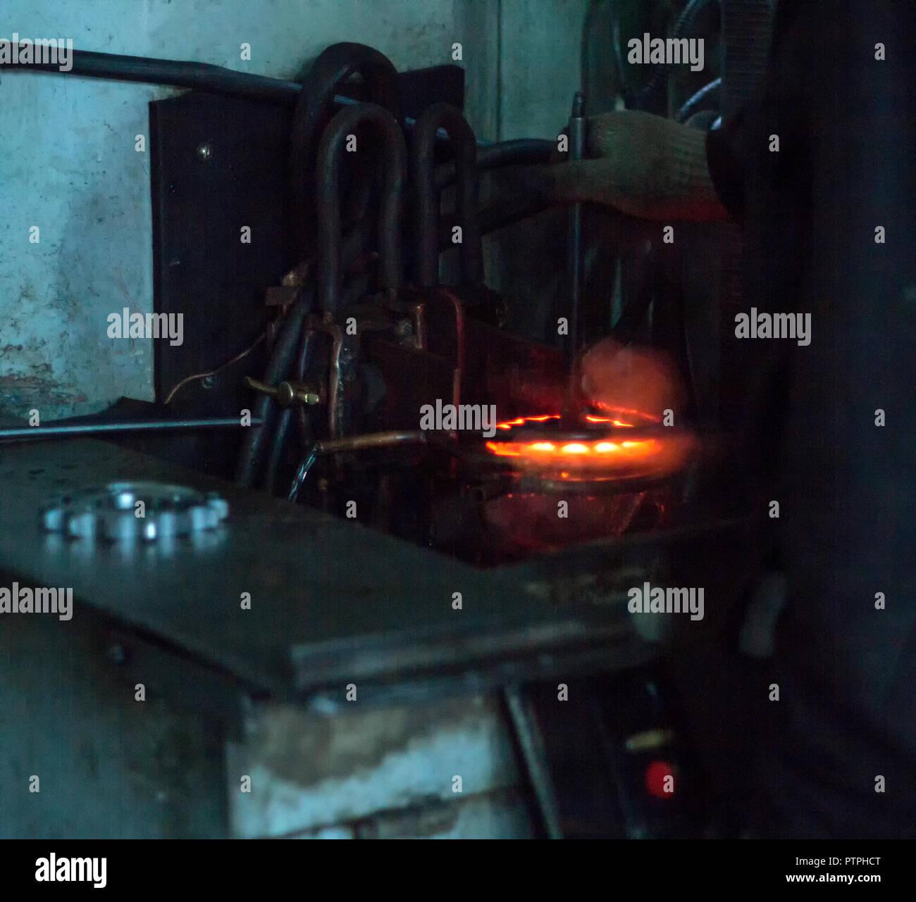 El trabajador realiza tratamiento térmico de endurecimiento del metal gear en una máquina especial, close-up, endurecimiento del metal, endurecimiento Imagen De Stock