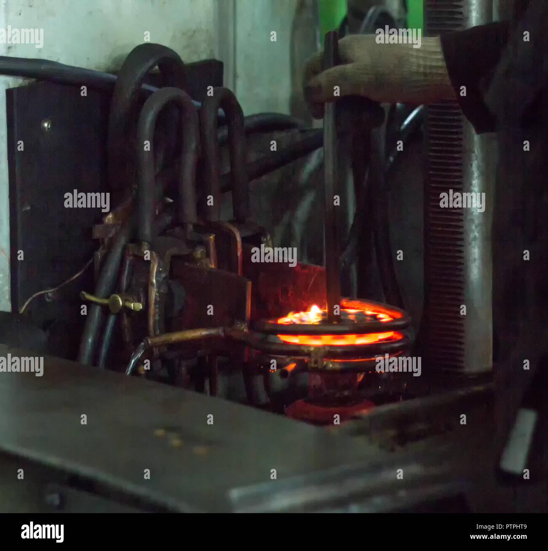 El trabajador realiza tratamiento térmico de endurecimiento del metal gear en una máquina especial, close-up, endurecimiento del metal Imagen De Stock