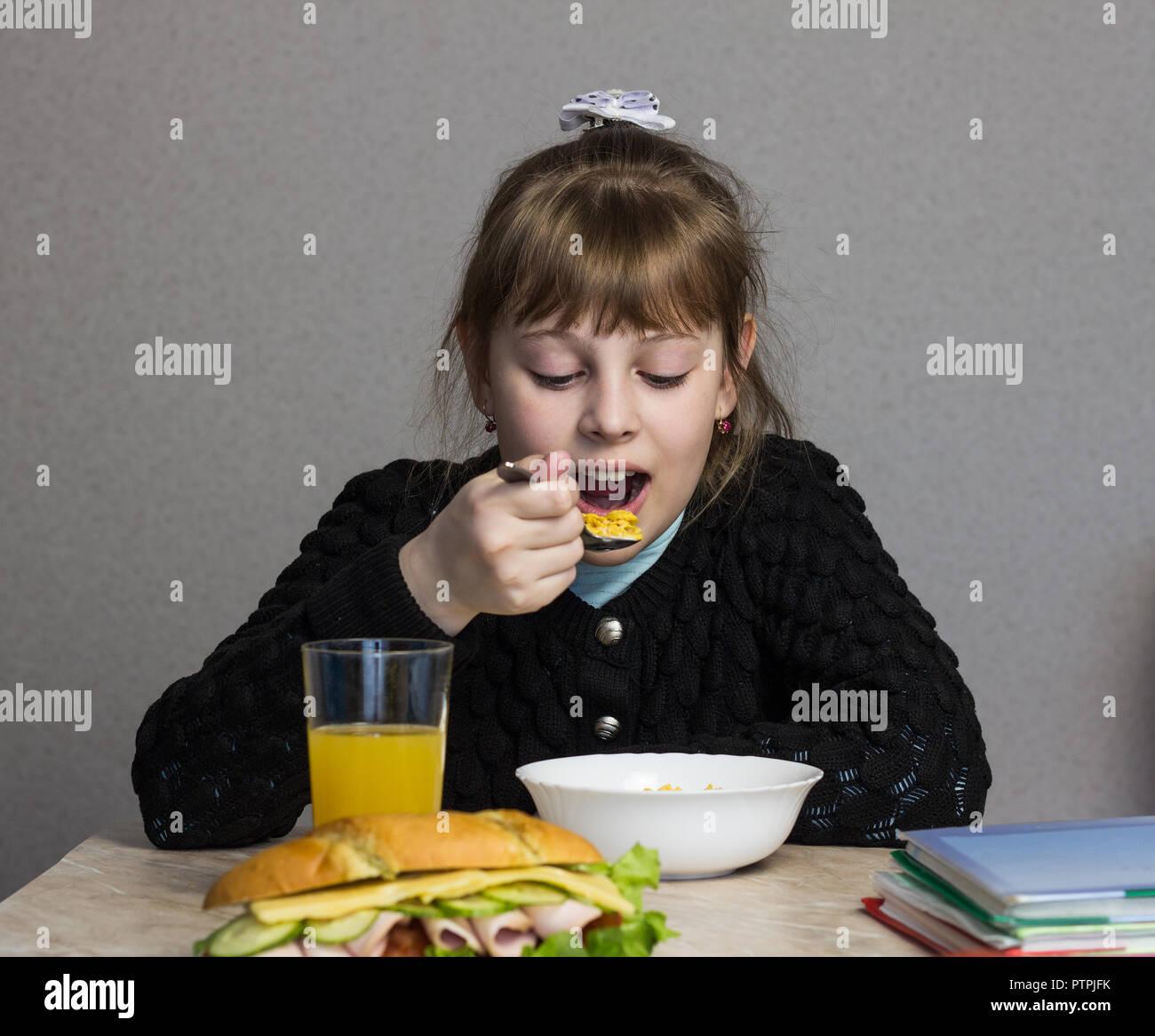 Una niña de 9-10 años el desayuno antes de salir para la escuela, sobre la mesa, un libro y un sándwich Imagen De Stock