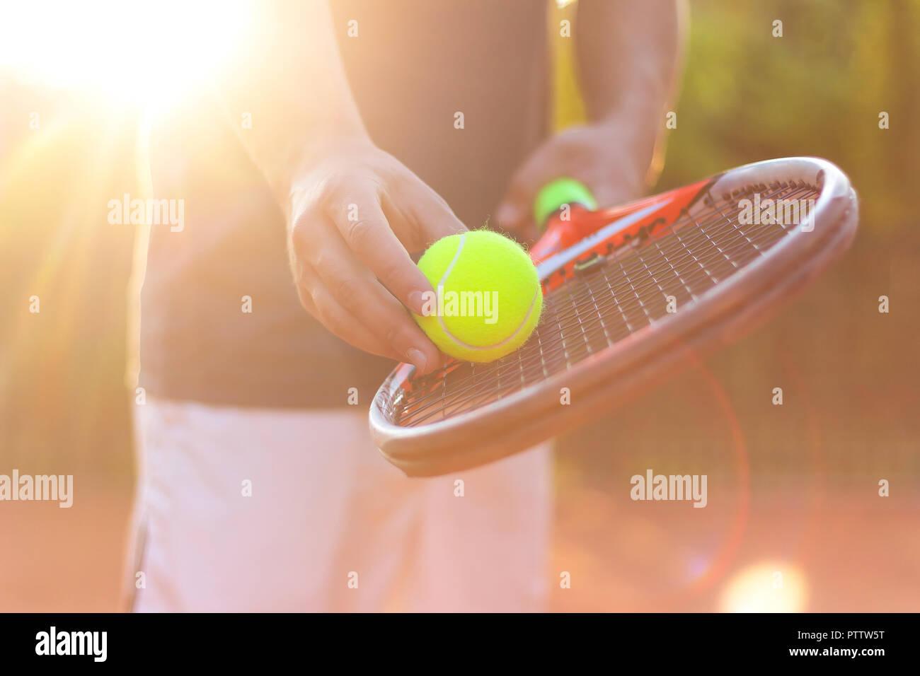 Un jugador de tenis se prepara para servir una pelota de tenis durante un partido con la luz del sol en segundo plano. Foto de stock