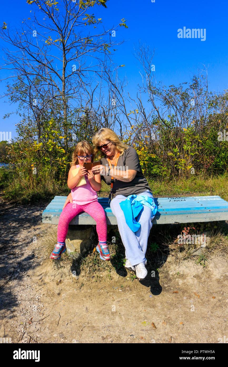 Grand niño gran madre enseñar cómo tomar foto a través de teléfono celular. Imagen De Stock