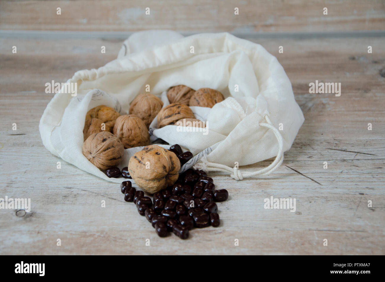 Las nueces en una bolsa con granos de chocolate sobre una mesa de cocina de madera Imagen De Stock