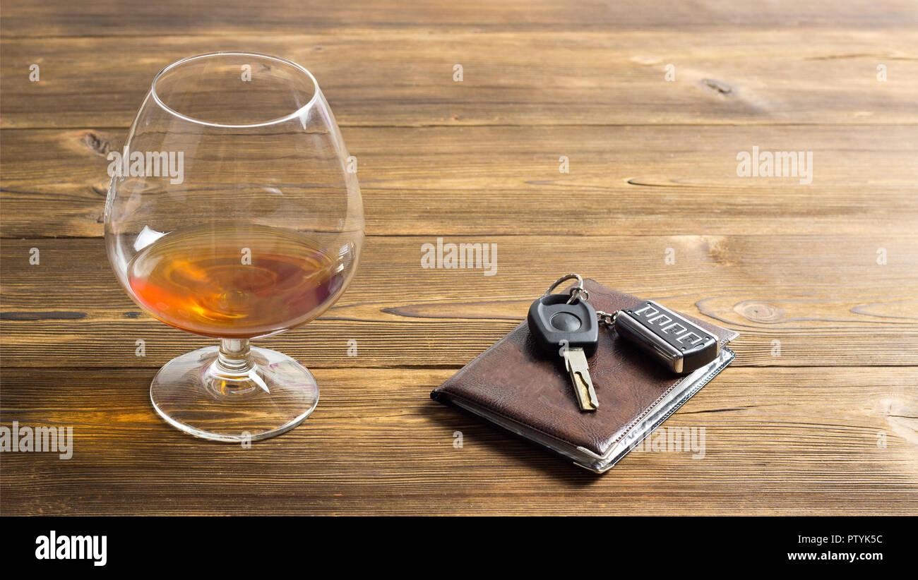 Las llaves del coche, el alcohol y la licencia de conductor, un fondo de madera Imagen De Stock