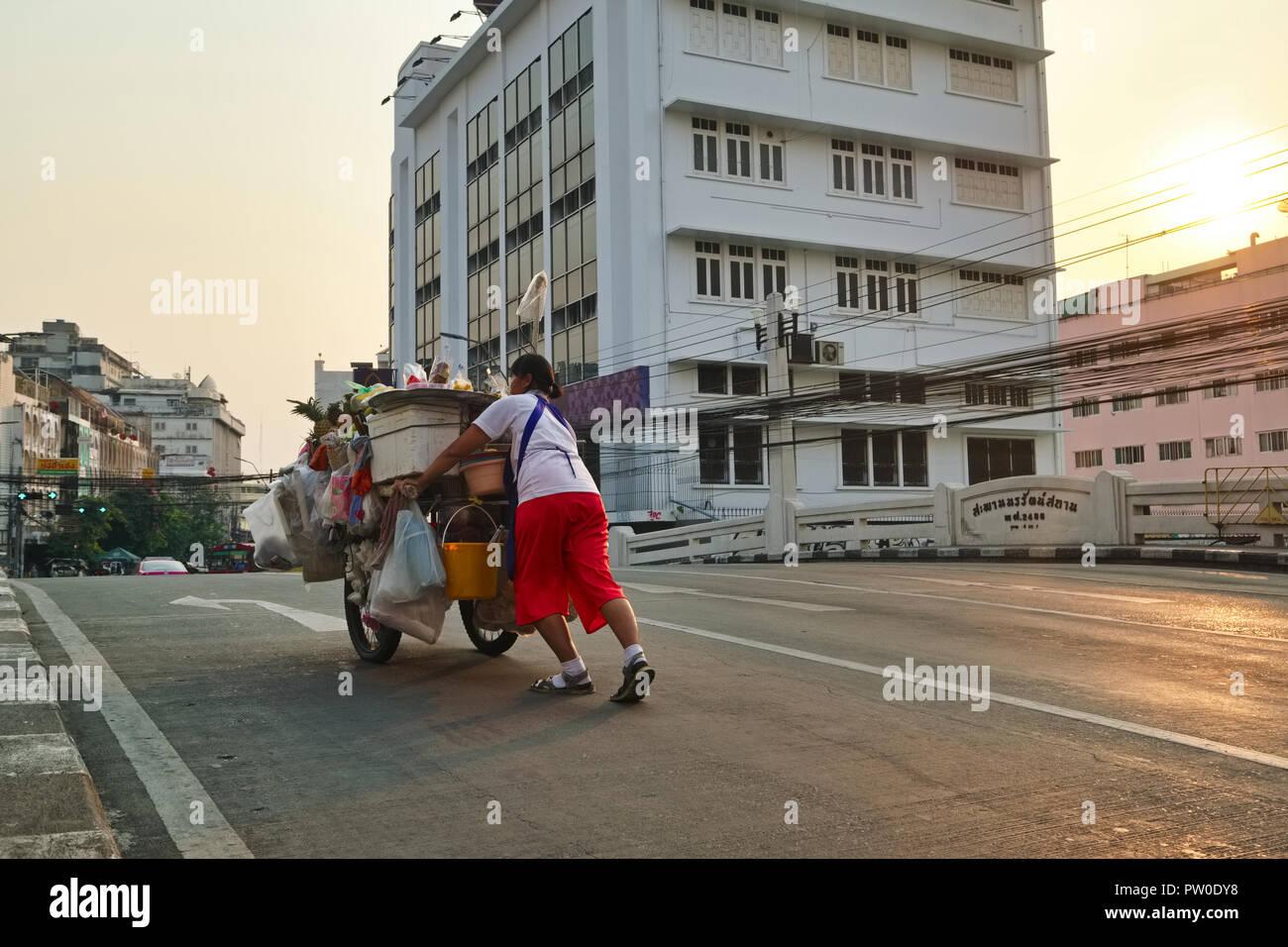 Vendedor de comida callejero en Bangkok, Tailandia, empujando su carro sobre un puente de Klong (canal) para establecer su puesto de comida por la noche Foto de stock