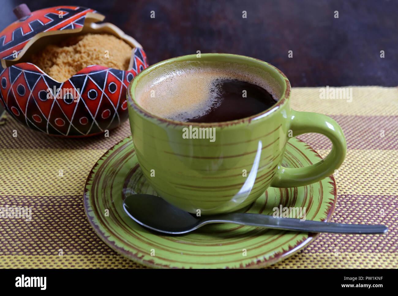 Café caliente en una taza verde con azúcar borrosa olla de azúcar moreno en el fondo sirvió en rayas un mantel. Imagen De Stock