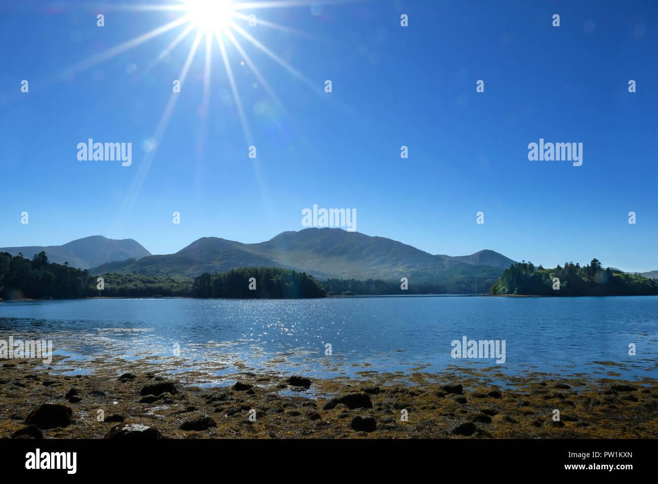 Kenmare River, en el condado de Kerry, Irlanda, costa con abundantes Lens Flare - John Gollop Foto de stock