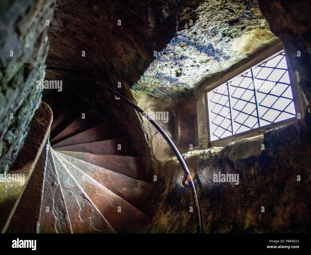 Escaleras de piedra espiral hacia abajo la vieja torre de castillo Foto de stock